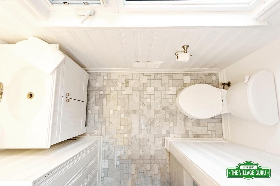 A sleek mosaic tile combined with white beadboard paneling createdhellip